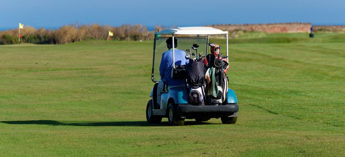 Two work colleagues sharing an electric golf buggy trip across the grass.